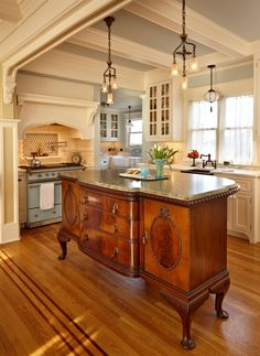 The #kitchen island uses an antique sideboard with a granite countertop placed on top! We love the idea of reusing old furnishings in a #home. www.budgetbathandkitchen.com