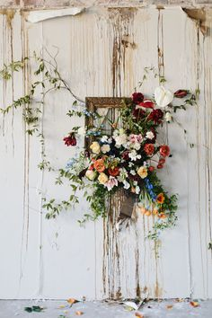 This wild backdrop isn't for everyone, however all can appreciate this amazing floral arrangement bursting out of a gilded frame. It would be a great addition to an industrial chic wedding setting.