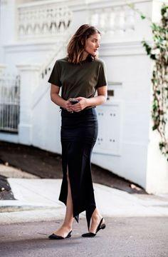 Sara Donaldson do Harper and Harley parada em frente à casa veste tshirt larga verde militar, saia midi lápis com fenda preta e sapatilhas de bico fino preta