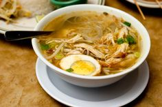 Soto ayam, an Indonesian version of chicken soup, is a clear herbal broth brightened by fresh turmeric and herbs, with skinny rice noodles buried in the bowl It is served with a boiled egg, fried shallots, celery leaves and herbs, and is hearty enough for a meal.
