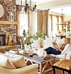 Rules of Texture: Warmth in this living room comes from the mix of textures, from the burlap curtains to the white linen slipcovers and the hide stool to the rough-hewn mantel on the local-stone fireplace.