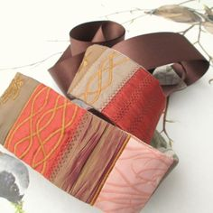 Obi pásek v podobných barvách (červeno-oranžovo-hnědá), určitě nemusí být stejný. Délka pásu 80-90 cm + stuha (celková délka aspoň 140-150 cm).