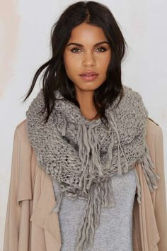 The Fringe With Benefits scarf comes in gray cable knit and features fringe ends, braided hem, and infinity scarf design.