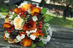 Burnt orange flowers, combined with miniature cream roses and bright red berries give this arrangement the perfect Autumnal look.