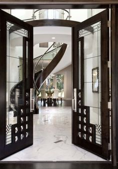 """decorative steel and glass double doors with sweeping steel and glass stairs.""…"