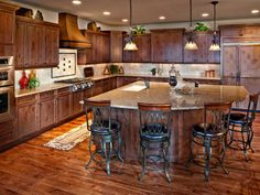 Rich brown cabinets and hardwood floor create this stunning traditional kitchen with ornate metal barstools around a large wood-paneled island.