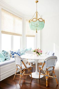 beach style dining area, with bench seat and french inspired cafe chairs, round white table, turquoise shell pendant, white, blue and turquoise cushions