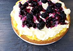 First Layer of Lemon Olive Oil Cake Covered with the Lemon Curd, Mascarpone Filling and Berry Sauce on a Rustic Table