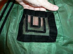 Trim detail, perhaps on an apron. [Note the way the ribbon is folded at the corners.  Those are mitered corners.
