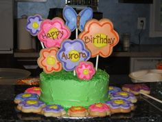 little girls birthday cake with decorated butterfly and flower cookies