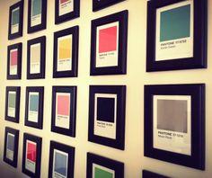 Grid of Pantone postcards in Ikea frames, office wall.
