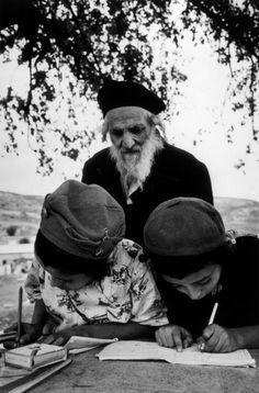 1950 International Center of Photography Galilee. Immigrant transit camp. (Rabbi supervisando a sus alumnos ortodoxos en un campo de inmigrantes) by R. Capa