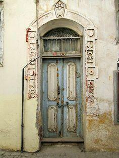Beautiful old door in Ayvalik. Balikesir, Turkey. Photo by Rezzan Akin. Old wooden gate, doorway, ornaments, detail, weathered, aged, cracks, beauty, entrance, portal, photo