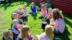 Meän Kulttuurikehdon kesäleirillä lapsia istumassa nurmikolla Seittenkaaressa.
