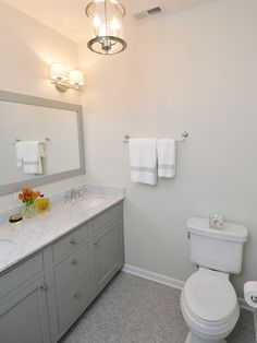 """Benjamin Moore's """"Fieldstone"""" gray painted bathroom vanity. Carrara marble counters and simple painted, framed mirrors. Pale gray wall color, nickel sconces and nickel and glass lantern pendant."""