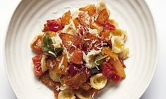 Round plate with a heap of orecchiette pasta and chunks of squash and tomato
