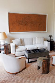 Contemporary art hangs above simple white furniture in a Jacques Grange–designed living room.