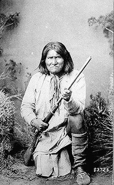 Geronimo (Goyathlay), a Chiricahua Apache; full-length,            kneeling with rifle. Photographed by Ben Wittick, 1887.