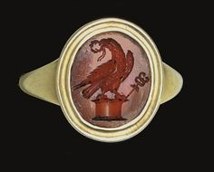 A roman ring set with a carnelian c. 1st 2nd cent A.D :The flat oval stone engraved with an eagle standing upon an altar, its head turned back, a laurel wreath in its beak, a caduceus to the right; mounted as a ring in a modern gold setting
