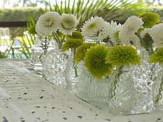single stem green and white button mums mixed in with white carnations placed in antique salt and pepper shakers