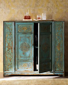 """Hand-Painted Wood Cabinet- Hand-Painted Wood Cabinet             Painted by hand in colorful Moroccan style, this tall, slender cabinet is teal with golden swirl designs. Sides are unfinished. Made of wood with two doors and one fixed shelf. Imported. 43""""W x 15""""D x 39""""T."""
