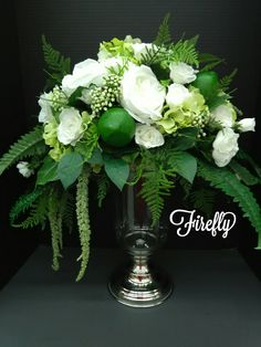 White roses and ferns with limes floral arrangement centerpiece