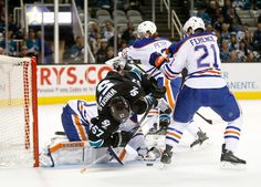 San Jose Sharks forward Tommy Wingels goes up-and-over Edmonton Oilers goaltender Ben Scrivens for a loose puck (Dec. 18, 2014).