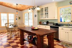 Kitchen with white cabinets and a large wood table used as an island. Heated floors in a checkerboard pattern. Some of the kitchen cabinets are glass-fronted.