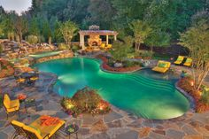 A true backyard resort, this poolscape features a cozy fireplace, multiple lounging spots and a freeform pool with a wading area and custom waterfall. Lewis Aquatech Pools, Chantily, Virginia http://www.luxurypools.com/swimmingpoolbuilder/Lewis-Aquatech-Pools?fid=365