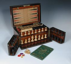Full Details for Lot 744 - Cheffins A Victorian walnut games compendium, the hinged lid and double-hinged front enclosing a turned wood chess set, leather bound board draughts pieces, and two removable trays, containing various counters, cribbage board and cards h:18 w:32 d:23 cm