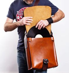 """Vinylize DJ leather bag. 100% Italian leather, and hand made in Hungary. Design by Vinylize.  Size: 32cm X 32cm X 10cm (12.5"""" X 12.5"""" X 2.5""""). Fits about 30 LPs or a 30cm laptop (12""""). Adjustable shoulder strap with anti slip strip. Back strap for carrying on your rolling luggage. All metal hardware: aluminium parachute buckle engraved with the Vinylize logo, steel adjusters. One large and one small removable inside pocket, perfect for Ipad or toilettries. Snap-on keyfob holder."""