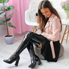 Black patent leather thigh boots, skirt, and pastel pink leather moto jacket.