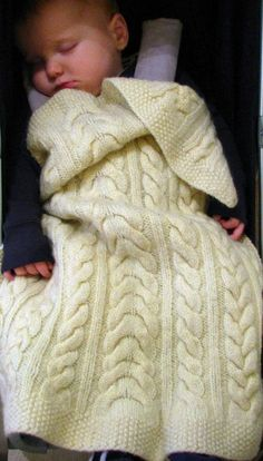 Free Knitting Pattern for Baby Cable Blanket - This car seat sized blanket features three alternating cable patterns and a seed stitch border. Designed by Alex Lawson. Knit in Aran weight yarn. Most Ravelrers found this fairly easy.