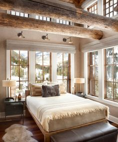To warm up this guest bedroom with its many windows, Kanning usedPhillip Jefferies' woven Herringbone Wall Covering on the walls.Above the bed are The Urban Electric Co.'s Maxine Sconces.Hubbardton Forge's Ondrian Lamps are on either side of the bed.