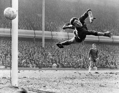 Chelsea goalkeeper Peter 'The Cat' Bonetti makes a flying save as teammate Eddie McCreadie watches on during the FA Cup semi-final against Liverpool, 1965