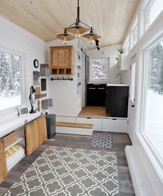 On the platform is the kitchen and bathroom. The kitchen has a cupboard that slides out from the entryway area, a large storage wall, open shelves, and a plant shelf in front of a window.