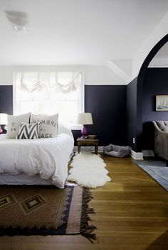 Navy blue bedroom with fuchsia lamps and vintage rug