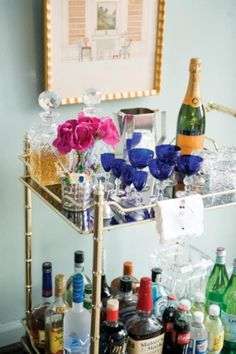 bar cart filled with drinks, cups, and ice for guests