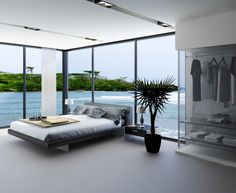 This modern bedroom has a cool color palette and floor-to-ceiling windows that have a beautiful view of the waterfront.