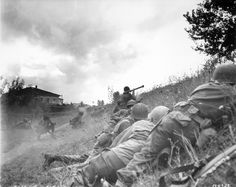 """""""Buffalo Soldiers"""" of the American 92nd Infantry Division, the only segregated African-American unit to see front line combat in Europe, take cover as another prepares to fire an M1 """"Bazooka"""" rocket launcher at a German machine gun nest. Lucca, Italy. 1944."""