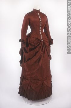 This dress can be precisely dated to 1884, as it was made for and worn at a wedding that year. It shows the hallmark silhouette of the mid-1880s: the shelf-like bustle from which the skirt hangs vertically, and the fitted bodice with low pointed waistline, high collar and closely fitted sleeves.