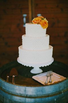 three tiered white wedding cake with orange flowers