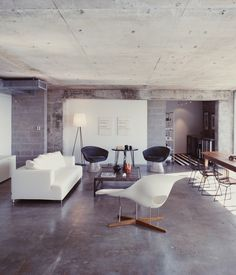 A Philippe Starck standing lamp and an Eames chaise longue bracket the living room; two Lawrence Weiner prints hang behind a pair of Warr...