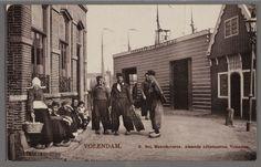 Zicht op de gemeentelijke visafslag met rechts het kantoortje. Op straat poseren vissers en een vrouw in dracht. 1900-1910 #NoordHolland #Volendam