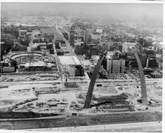 1965 -- Aerial view of the St. Louis riverfront and downtown St. Louis looking west at the construction of Busch Stadium and the Gateway Arch.