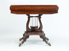 <b>JOSEPH BARRY (ATTRIBUTION), CLASSICAL CARVED MAHOGANY AND FIGURED MAHOGANY CROSS LYRE-BASE CARD TABLE, PHILADELPHIA, C. 1820</b> <br /> Carved mahogany, figured mahogany veneer, white pine and brass.  29 x 36 x 18 in. <br />  <br /> Note: For a similar example, <i>Boor Philadelphia Empire Furniture,</i> pg. 188, figure 63. <br />  <br /> The Collection of Judith Hollander <br />