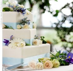 A three-tiered cake frosted in buttercream with light blue ribbons around the base of each tier. Fresh flowers in the wedding colors, including daisies, roses, and irises, sat atop the tiers.
