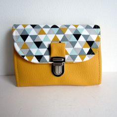 Très original, ce porte feuille, porte carte, et porte monnaie en petite taille. Réalisé en coton Triangles jaune/ gris pour le rabat et en simili...