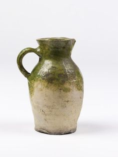 Physical description  Jug of buff earthenware, partly covered with a green glaze over a white slip. Ovoid body, spreading mouth pinched in front to form a lip, loop handle.  Place of Origin  Surrey, England (made) Hampshire, England (possibly, made) Date  ca. 1500-1600 (made)