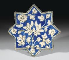An Ilkhanid pottery star tile, Persia, early 14th century moulded in relief and decorated in underglaze cobalt blue outlined in black with lotus head and rosette stem, white border 20.2cm. diam.